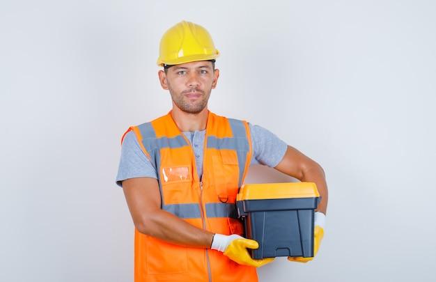 ユニフォーム、ヘルメット、手袋、正面のツールボックスを保持している男性のビルダー。 無料写真