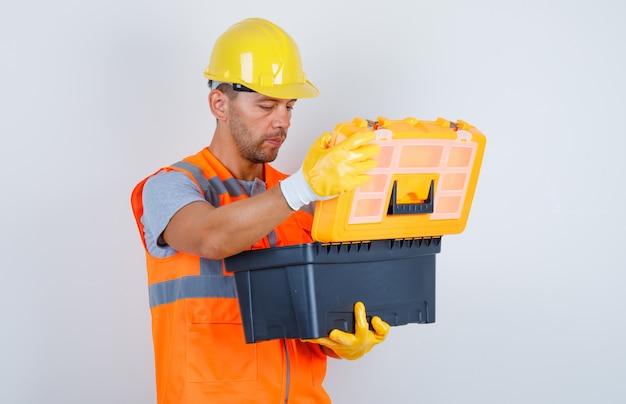 男性ビルダーが制服、ヘルメット、手袋、正面のプラスチックツールボックスを開きます。 無料写真