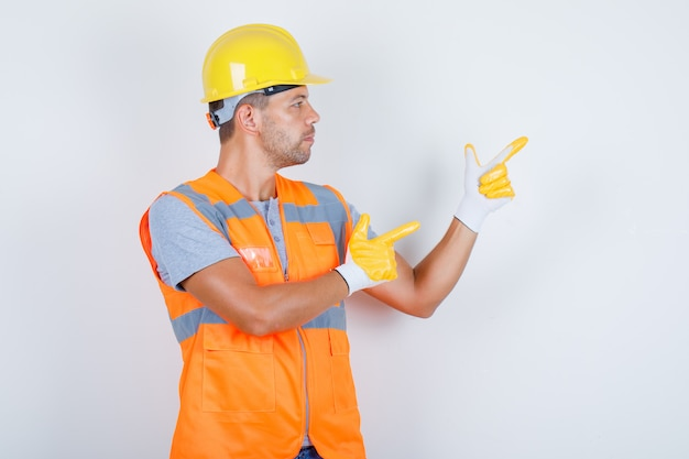 Male builder pointing fingers at something in uniform and looking confident, front view Free Photo