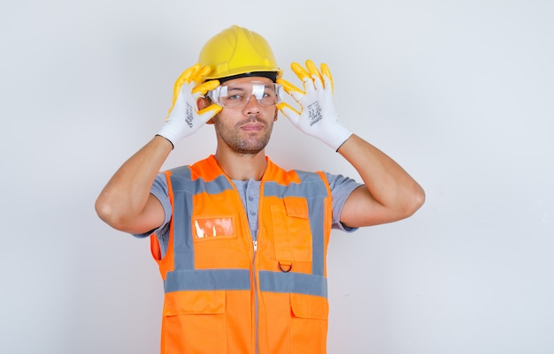 Male builder in uniform, helmet, gloves wearing safety glasses, front view. Free Photo