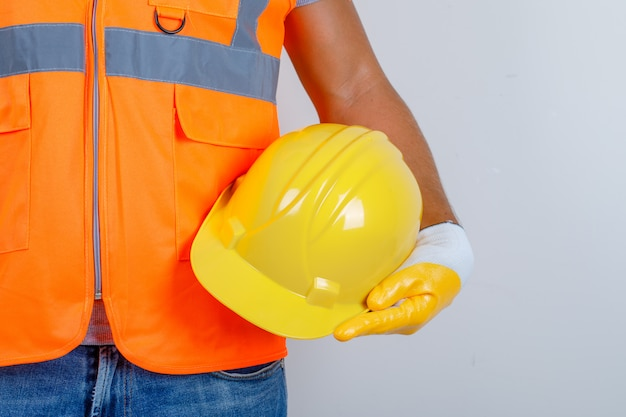 Male builder in uniform, jeans, gloves holding helmet in his hand, front view. Free Photo