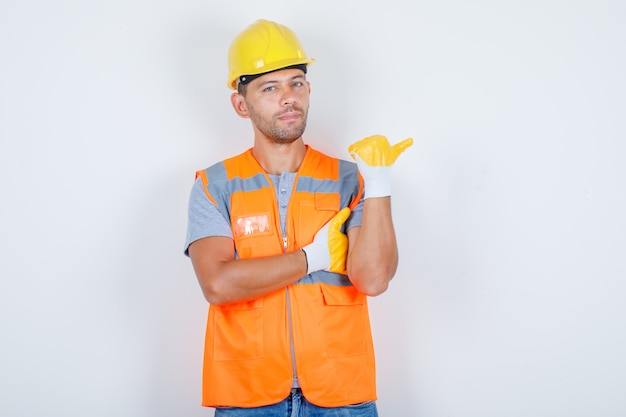 Male builder in uniform pointing away while standing and looking confident, front view. Free Photo