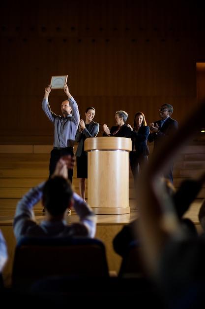 Male business executive receiving award Free Photo