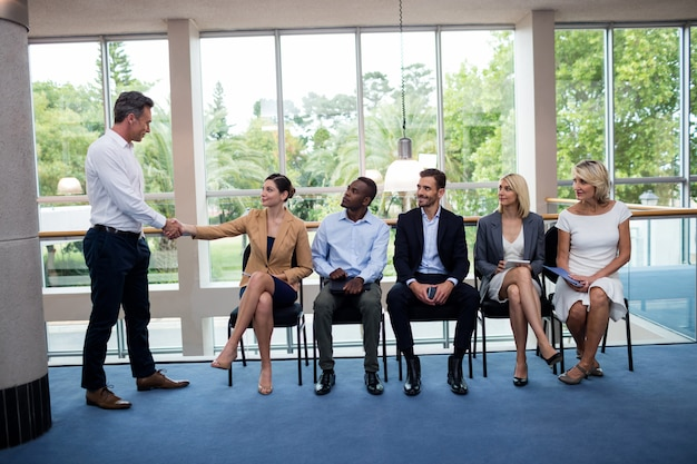 Male business executive shaking hands with a participant Premium Photo