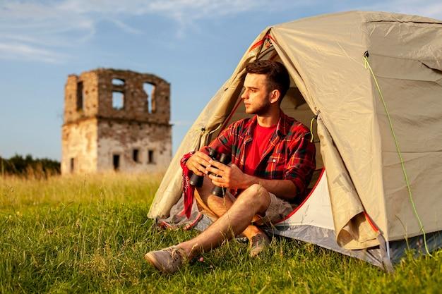Maschio in tenda da campeggio con binocolo Foto Gratuite