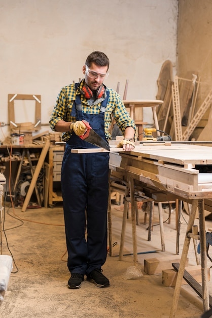 Male carpenter cutting the wooden plank with handsaw Free Photo