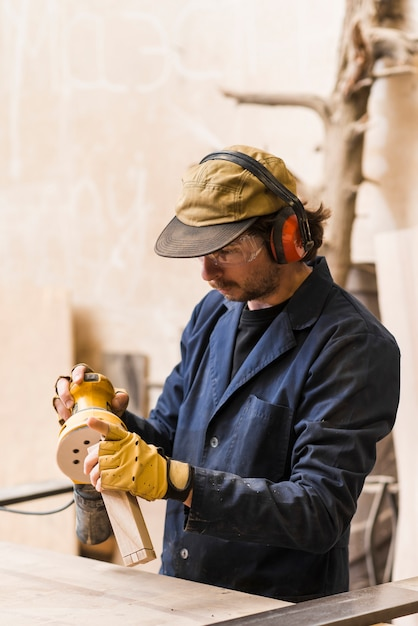 Male carpenter processes the block with a random orbit sander in the workshop Free Photo