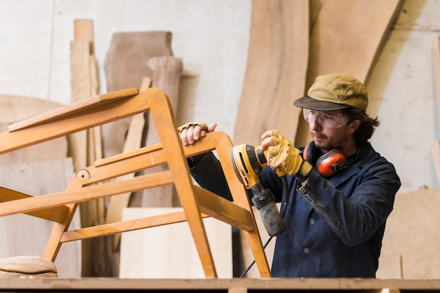 Male carpenter sanding a wood with orbital sander in a workshop Free Photo
