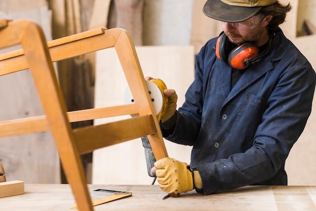 Male carpenter sanding a wood with sander on workbench Premium Photo