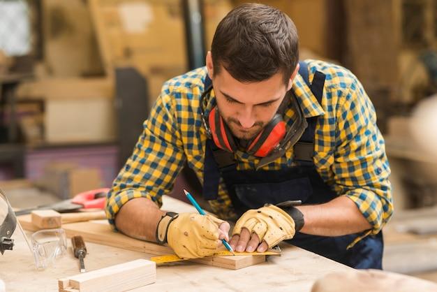 A male carpenter taking the measurement of wooden block on workbench Free Photo