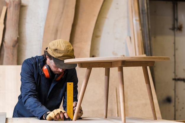 Male carpenter taking measurement of wooden table with ruler Premium Photo