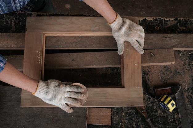 The male carpenter uses sandpaper to polish the woodwork. Premium Photo