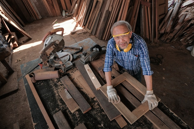 The male carpenter uses sandpaper to polish the woodwork. Premium Photo