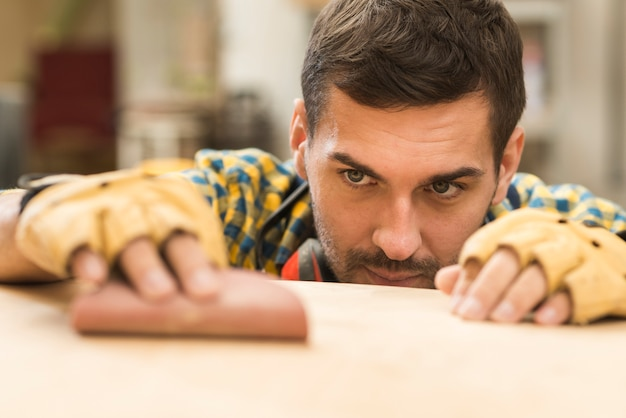 A male carpenter using sandpaper on wooden surface Free Photo