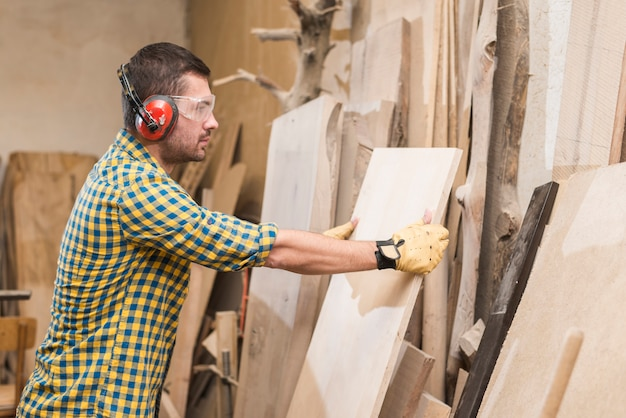 A male carpenter wearing protective safety glasses holding wooden plank in the workshop Free Photo