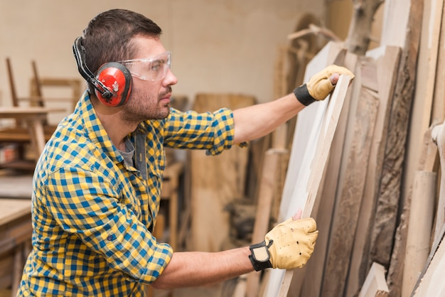 Male carpenter wearing safety glasses checking wooden plank in the workshop Free Photo