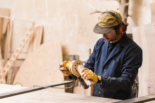 A male carpenter working with orbital sander for shaping wooden block Free Photo