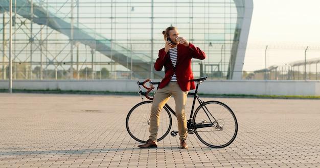 Мужской случайный красивый велосипедист в красной куртке, сидя на велосипеде, потягивая горячий напиток и разговаривая по мобильному телефону. в большом стеклянном современном здании. кавказский мужчина пьет кофе. и разговаривает по мобильному телефону. Premium Фотографии