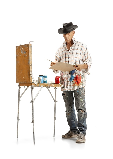 Male caucasian artist, painter at work isolated on white studio. Free Photo