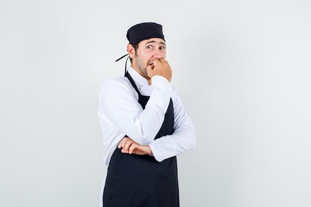 男性シェフが制服、エプロン、ストレスの多い正面図で爪を噛んでいます。 無料写真