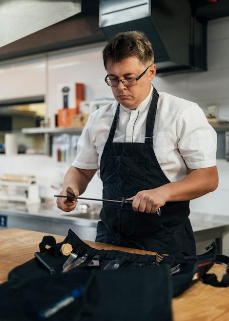 キッチンでクリップボードをチェックする男性シェフ Premium写真