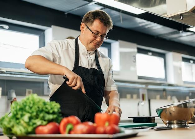キッチンでトマトを刻む男性シェフ 無料写真