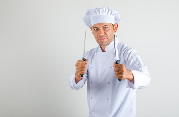 男性シェフが金属のナイフをユニフォームと帽子に押しながら自信を持って 無料写真