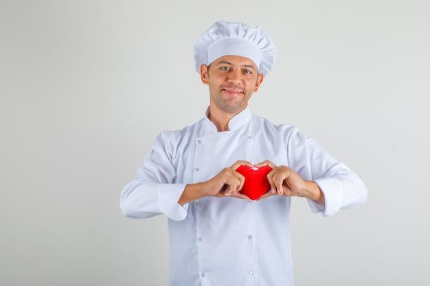 Мужской шеф-повар держит красное сердце и улыбается в шляпе и униформе и выглядит счастливым Бесплатные Фотографии