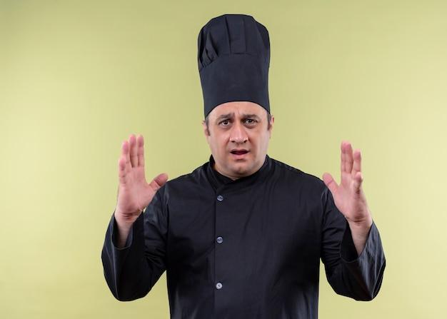 男性シェフの料理人は黒い制服を着て、大きなサイズのサインを示す手で身振りで示す帽子を調理し、驚いて、緑の背景の上に立っているシンボルを測定します 無料写真