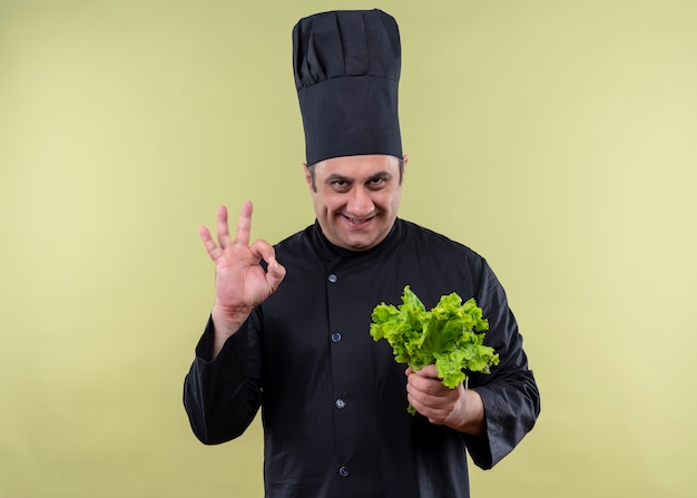 黒の制服を着た男性シェフの料理人と緑の背景の上に立っているokサインを示して笑顔の新鮮なレタスを保持している帽子を調理します 無料写真