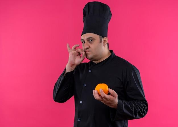 黒の制服を着た男性シェフの料理人とピンクの背景の上においしい立っているための兆候を示すオレンジ色の果物を保持している料理人 無料写真