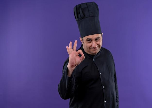 男性シェフの料理人は黒い制服を着て、紫色の背景の上に立っているokサインを示して笑顔のカメラを見て帽子を調理します 無料写真