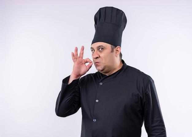 黒の制服を着て、白い背景の上においしい立っているための兆候を示す帽子を調理する男性シェフ 無料写真
