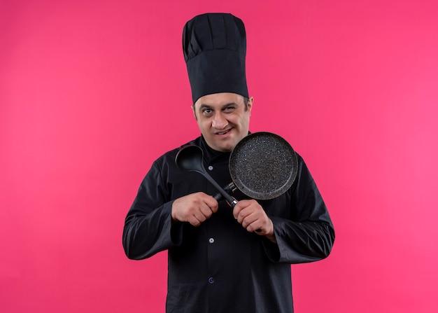 Cuoco unico maschio che indossa l'uniforme nera e cappello da cuoco che tiene la padella e il cucchiaio che attraversano le mani guardando la fotocamera con il sorriso in piedi su sfondo rosa Foto Gratuite