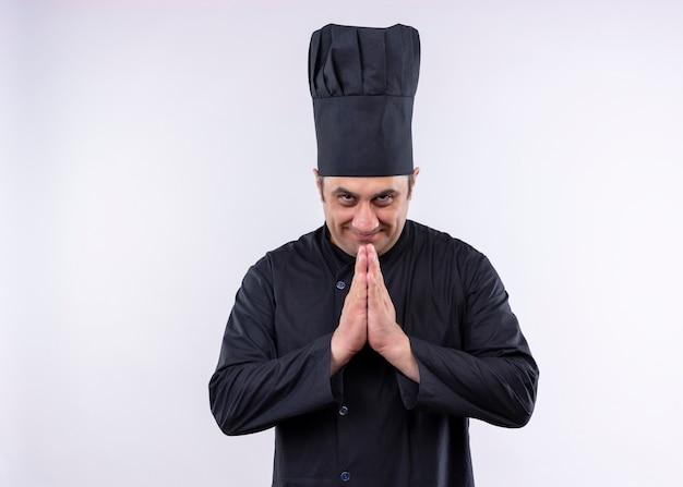 Cuoco unico maschio che indossa l'uniforme nera e cappello da cuoco che tengono le mani insieme sentendosi grato in piedi su sfondo bianco Foto Gratuite