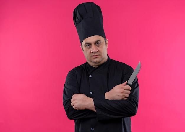 Cuoco unico maschio che indossa l'uniforme nera e cappello da cuoco che tiene il coltello da cucina con le mani incrociate che guarda l'obbiettivo con il viso seriouis in piedi su sfondo rosa Foto Gratuite