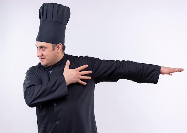 Cuoco unico maschio che indossa l'uniforme nera e cappello da cuoco che guarda da parte gesticolando con la mano che indica con il braccio di lato in piedi su sfondo bianco Foto Gratuite