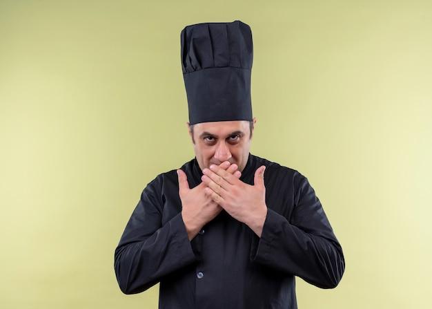 Cuoco unico maschio che indossa l'uniforme nera e cappello da cuoco che guarda l'obbiettivo sorridente che copre la bocca con le mani in piedi su sfondo verde Foto Gratuite