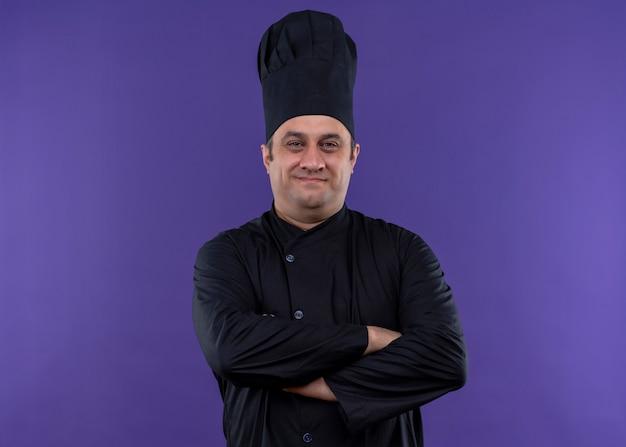 Cuoco unico maschio che indossa l'uniforme nera e cappello da cuoco che guarda l'obbiettivo con un sorriso sicuro sul viso con le mani incrociate sul petto in piedi su sfondo viola Foto Gratuite