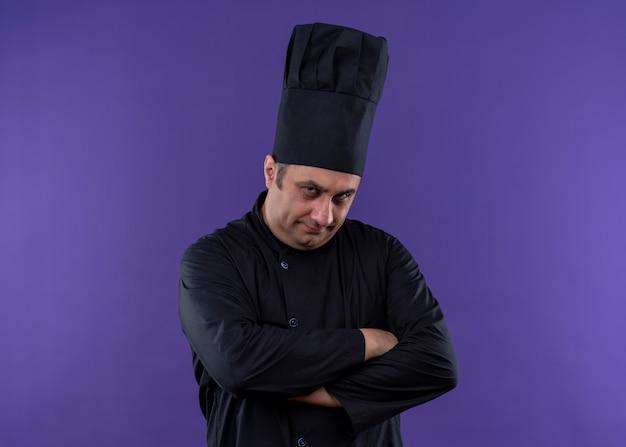 Cuoco unico maschio che indossa l'uniforme nera e cappello da cuoco che guarda l'obbiettivo con il viso accigliato con espressione scettica con le mani incrociate sul petto in piedi su sfondo viola Foto Gratuite