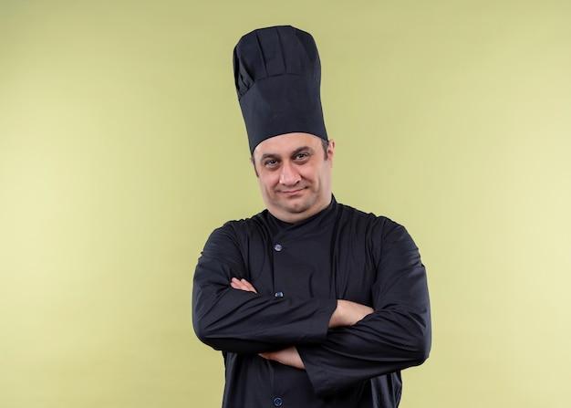 Cuoco unico maschio che indossa l'uniforme nera e cappello da cuoco guardando la fotocamera con le mani incrociate guardando fiducioso in piedi su sfondo verde Foto Gratuite