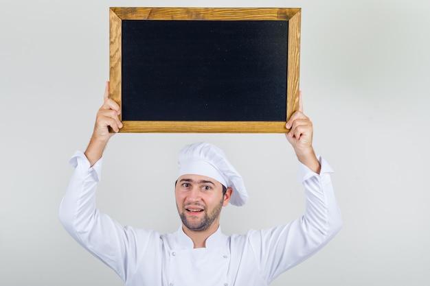 Cuoco unico maschio che tiene lavagna sopra la testa in uniforme bianca e guardando positivo. Foto Gratuite