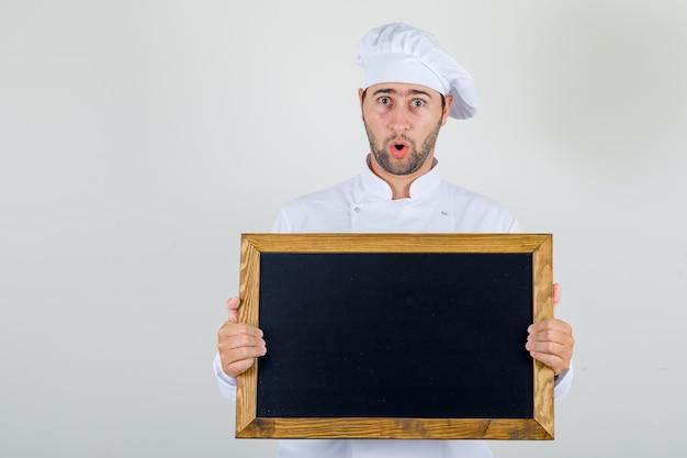 Шеф-повар-мужчина держит доску в белой форме и выглядит шокированным Бесплатные Фотографии