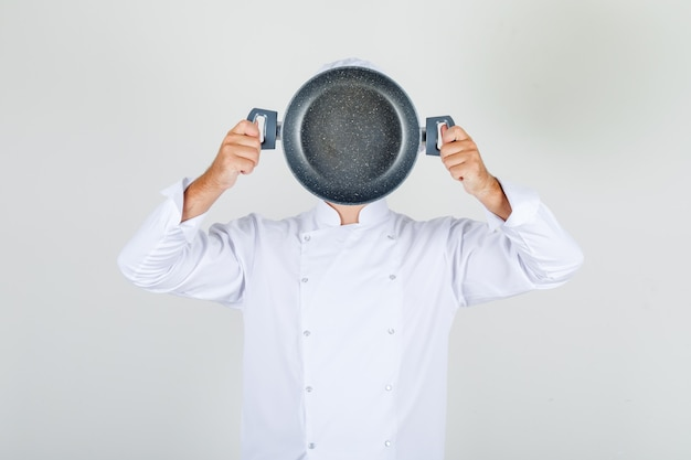Male chef holding empty pan over his face in white uniform Free Photo