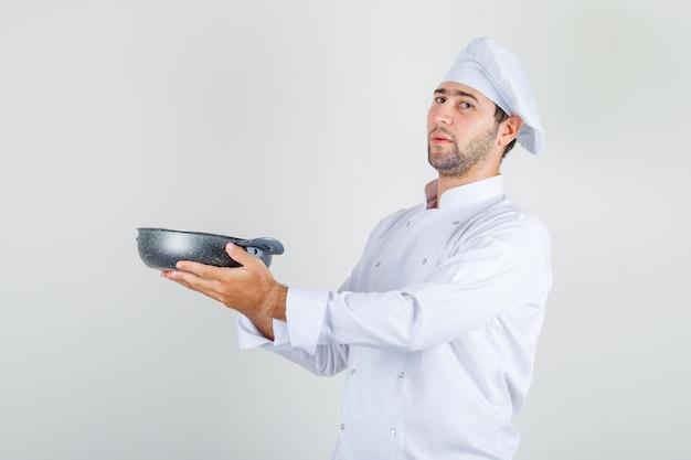 白い制服を着たパンを押しながら誇りに思っている男性シェフ 無料写真
