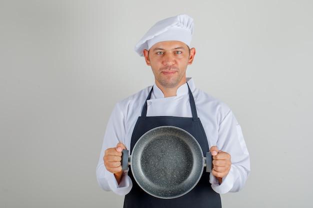 帽子、エプロン、制服の空のパンを押しながら喜んでいる男性シェフ 無料写真