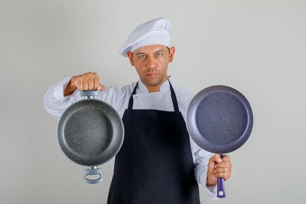 空の鍋を保持している帽子、エプロン、制服を着た男性シェフ 無料写真