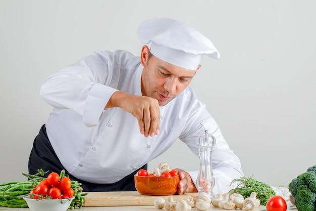 制服を着た男性シェフ、帽子、エプロンがキッチンの食べ物にスパイスを追加 無料写真