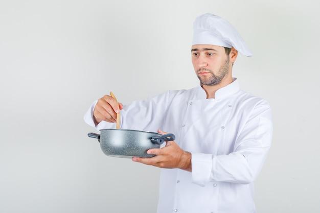 白い制服を着た木のスプーンでスープを混ぜる男性シェフ 無料写真