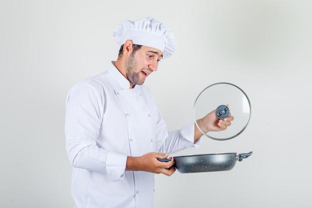 白い制服を着たパンの蓋を開けて陽気な男性シェフ。 無料写真